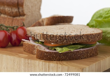 Freshly made ham salad sandwich on chopping board with loaf and vegetables - stock photo