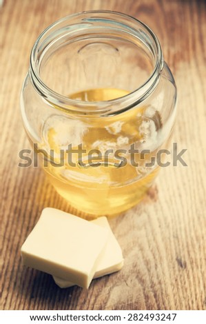 Freshly made liquid clarified butter Ghee in glass jar on wooden background - stock photo