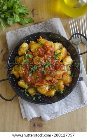 Freshly made patatas bravas topped with chopped parsley - stock photo