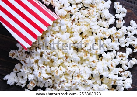 Freshly made popcorn on a wooden table - stock photo
