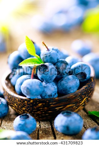 Freshly picked blueberries in wooden bowl. Juicy and fresh blueberries with green leaves on rustic table. Bilberry on wooden Background. Blueberry antioxidant. Concept for healthy eating and nutrition - stock photo