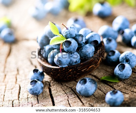 Freshly picked blueberries in wooden bowl on rustic table. Blueberry with .green leaves closeup over wooden background. Concept of healthy eating. Bilberries. Diet. Dieting. Vitamins