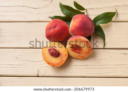 Freshly picked organic peaches with leaves from tree - top view - stock photo