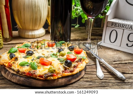Freshly pizza served with red wine - stock photo