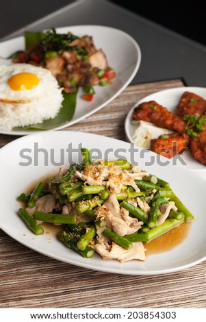 Freshly prepared Asian style chicken and asparagus stir fry with garlic and a variety of other Thai food dishes in the background. - stock photo