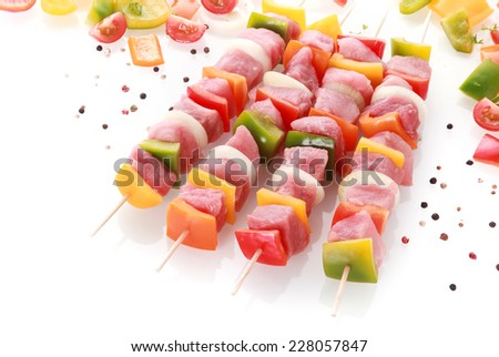 Freshly prepared colorful meat kebabs with diced red, yellow, green bell pepper, onion and tomato threaded on skewers seasoned with peppercorns ready for cooking - stock photo
