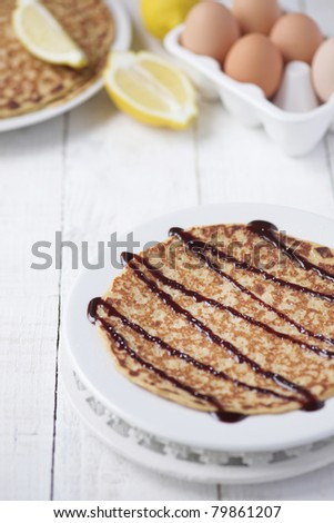 Freshly prepared crepes with chocolate sauce - shallow dof - stock photo