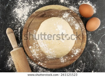 Freshly prepared dough on a wooden board. Rolling pin and egg on table. Top view - stock photo