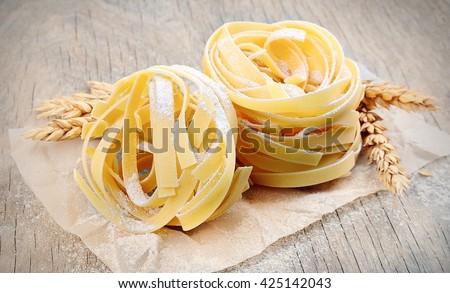 Freshly prepared fettuccine pasta closeup. Pasta tagliatelle with wheat. - stock photo