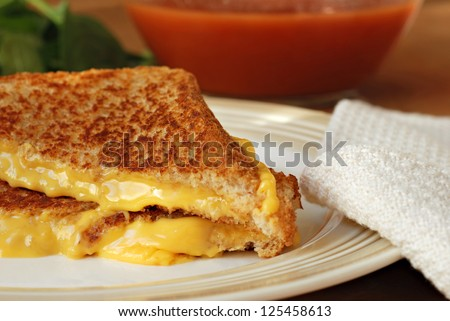 Freshly prepared grilled cheese sandwich with soup and fresh spinach in background.  Macro with shallow dof. - stock photo