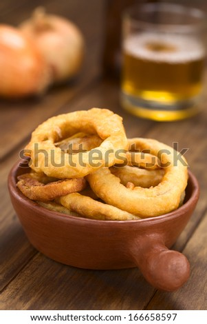 Freshly prepared homemade beer-battered onion rings in a rustic bowl with beer in the back (Selective Focus, Focus on the front of the onion rings on top) - stock photo