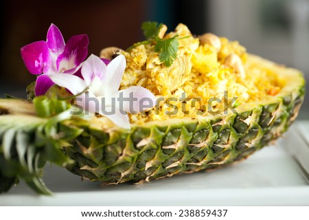 Freshly prepared pineapple fried rice served inside of a pineapple carved like a bowl. - stock photo