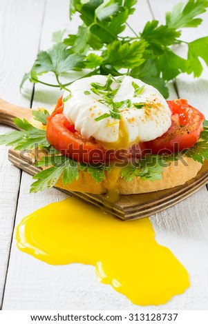 Freshly prepared poached egg on toast with tomato, parsley and pour the yolk on a white wooden table - stock photo