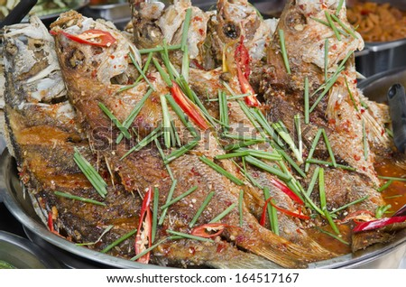 Freshly prepared Thai style whole fish red snapper dinner with tamarind sauce - stock photo