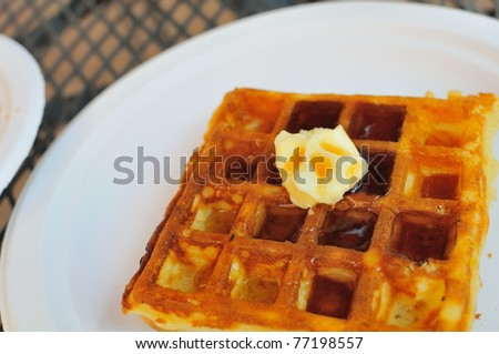 Freshly prepared waffle with butter and topped with sweet maple syrup. - stock photo