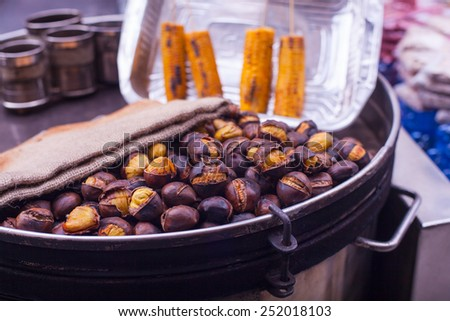 Freshly roasted chestnuts inside a iron plate - stock photo