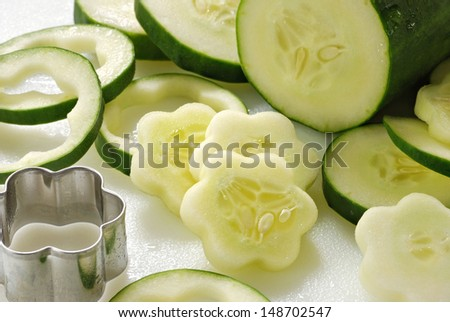Freshly sliced cucumbers being cut into flower shapes (with mini cookie cutter) on white cutting board.  Closeup with shallow dof. - stock photo