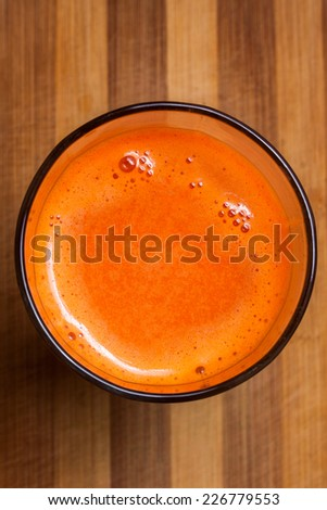 Freshly Squeezed Carrot Juice on a wooden board - stock photo