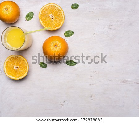 freshly squeezed juice from oranges in a glass with a straw, spread out around the oranges and mint on wooden rustic background top view close up - stock photo