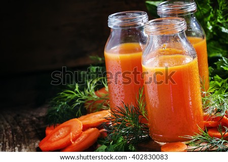 Freshly squeezed juice of carrots in glass bottles, vintage wooden background, selective focus - stock photo