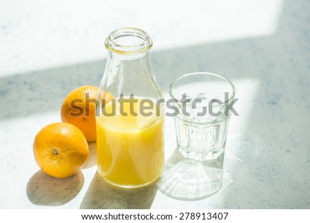 Freshly squeezed orange juice in a bottle. An empty glass and whole oranges are on side. - stock photo
