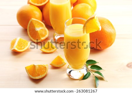 Freshly squeezed orange juice on wooden table - stock photo