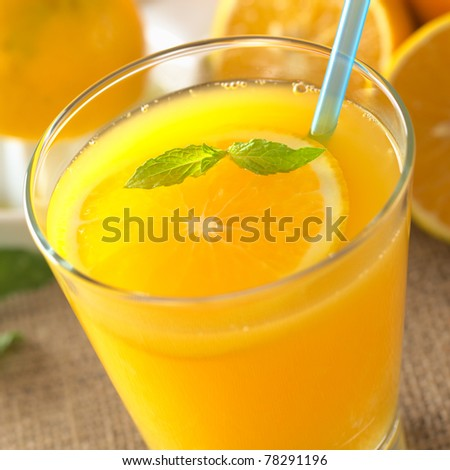 Freshly squeezed orange juice with orange slice and mint leaf on top of the juice with a blue drinking straw (Selective Focus, Focus on the mint leaf on top of the juice) - stock photo