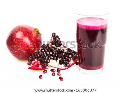 Freshly squeezed pomegranate juice in a glass, a pomegranate and half of pomegranate on white background - stock photo