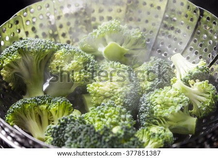 Freshly steamed green broccoli in skimmer pot with steam - stock photo