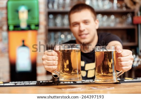 Freshly tapped beer. Selective focus on close up of glasses with beer which cheerful young bartender stretches out and smiles - stock photo