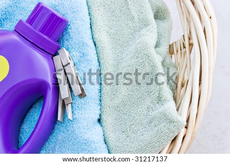 Freshly washed towels in a laundry basket with detergent - stock photo