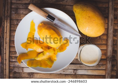 freshness fruit mango  lying on a white plate with knife. Fresh shake with milk and straw on brown board rustic - stock photo