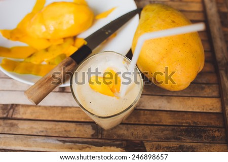 freshness fruit mango  lying on a white plate with knife. Fresh shake with shape heart love  mango slices milk and straw on brown board rustic - stock photo