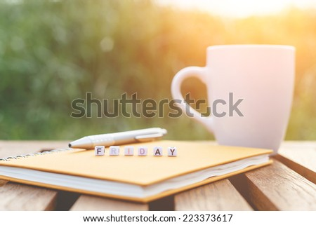 Friday written in letter beads and a coffee cup on table - stock photo