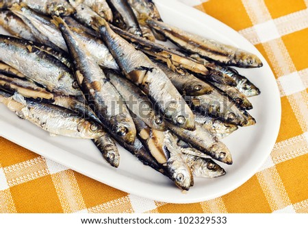 Fried anchovies on a plate (shallow dof) - stock photo