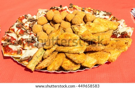 Fried appetizers on a table with red paper tablecloth - stock photo