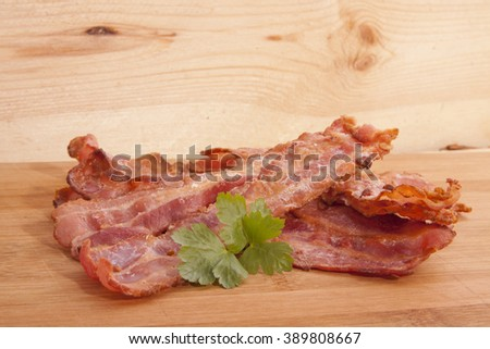 Fried bacon on wood with green parsley - stock photo
