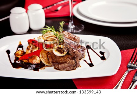 Fried beef mignon with vegetables and soy sauce served on white plate in restaurant - stock photo