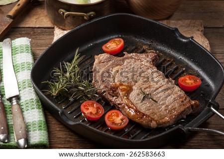 Fried beef steak in a frying pan. - stock photo