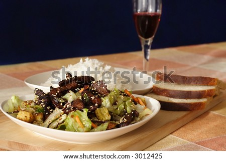 Fried beef with vegetables, sesame seeds, mushrooms, teriyaki sauce, rice and bread. - stock photo