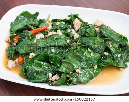 Fried bitter gourd leaf with pork, Thai cuisine - stock photo