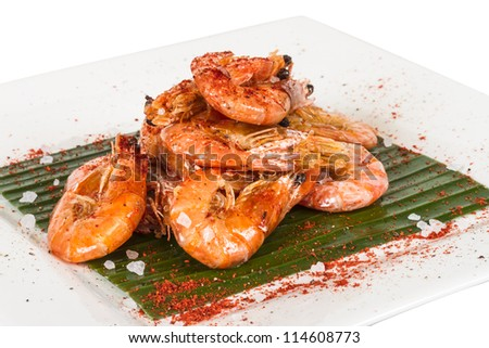fried black tiger prawns with herbs and spices on banana leaf - stock photo