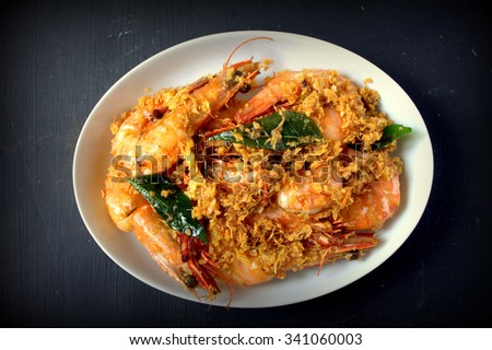 Fried Butter prawn with cereal served on wooden table background. famous food in south east asian - stock photo