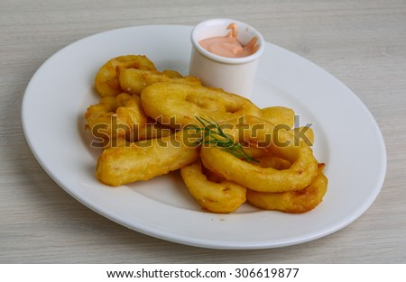 Fried calamari rings with sauce and dill - stock photo