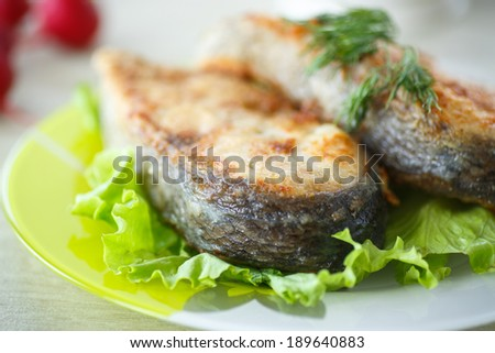 fried carp in large chunks on a plate with salad - stock photo