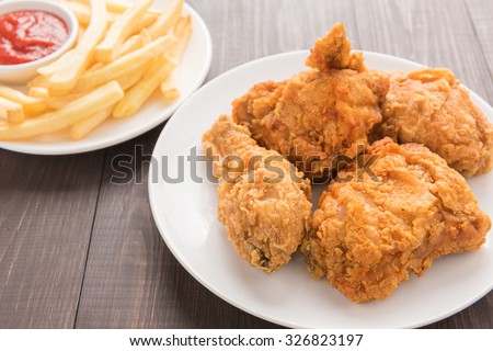 fried chicken and french fries on a wooden background. - stock photo