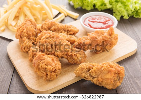 fried chicken drumstick and french fries on wooden table. - stock photo