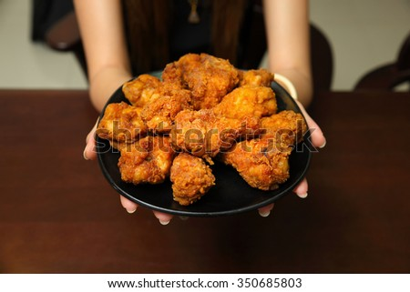 Fried chicken in hand on wooden background design - stock photo