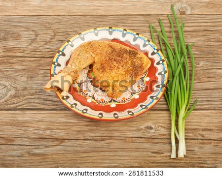 Fried chicken leg on a plate with fresh green onion on a wooden table background - stock photo