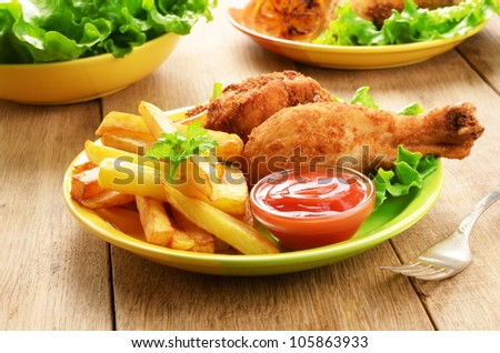 Fried chicken legs with french fries on the table - stock photo